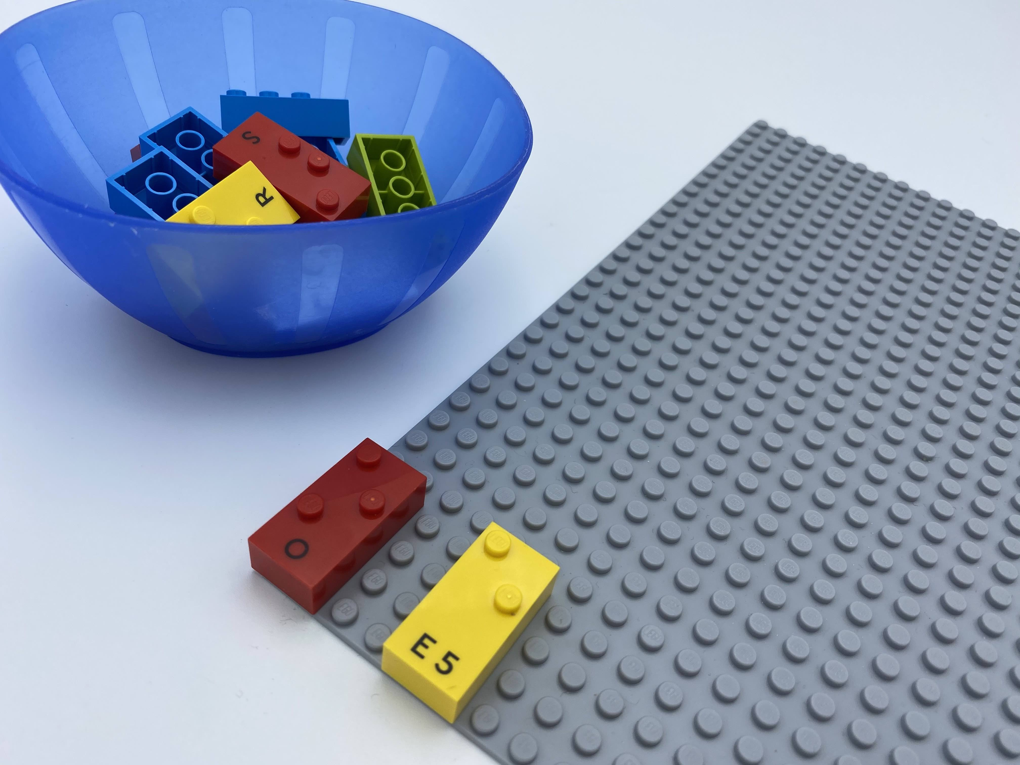A horizontal brick in the top left corner of the base plate, one 2 spaces below, bricks in bowl.