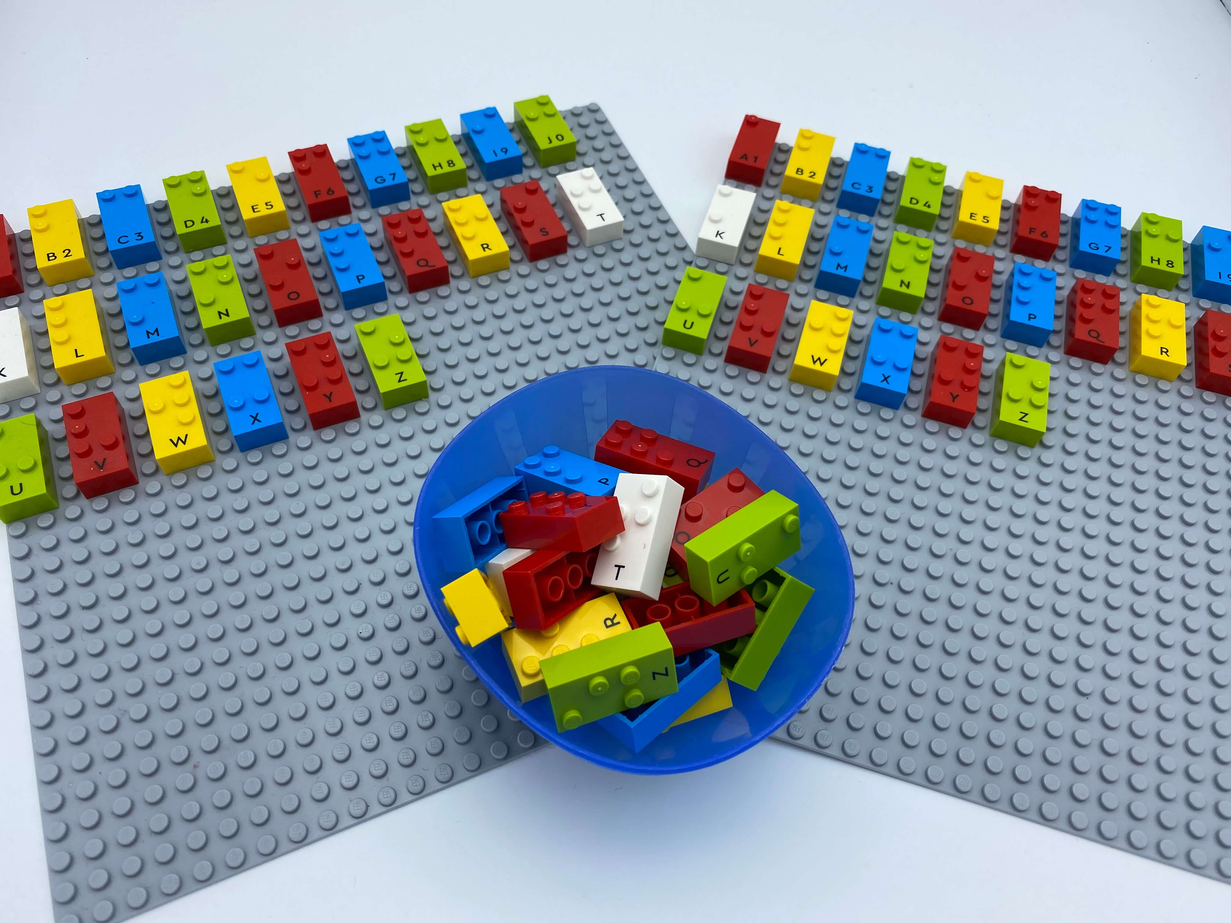 2 base plates with an entire alphabet of letters bricks each, a bowl with bricks.