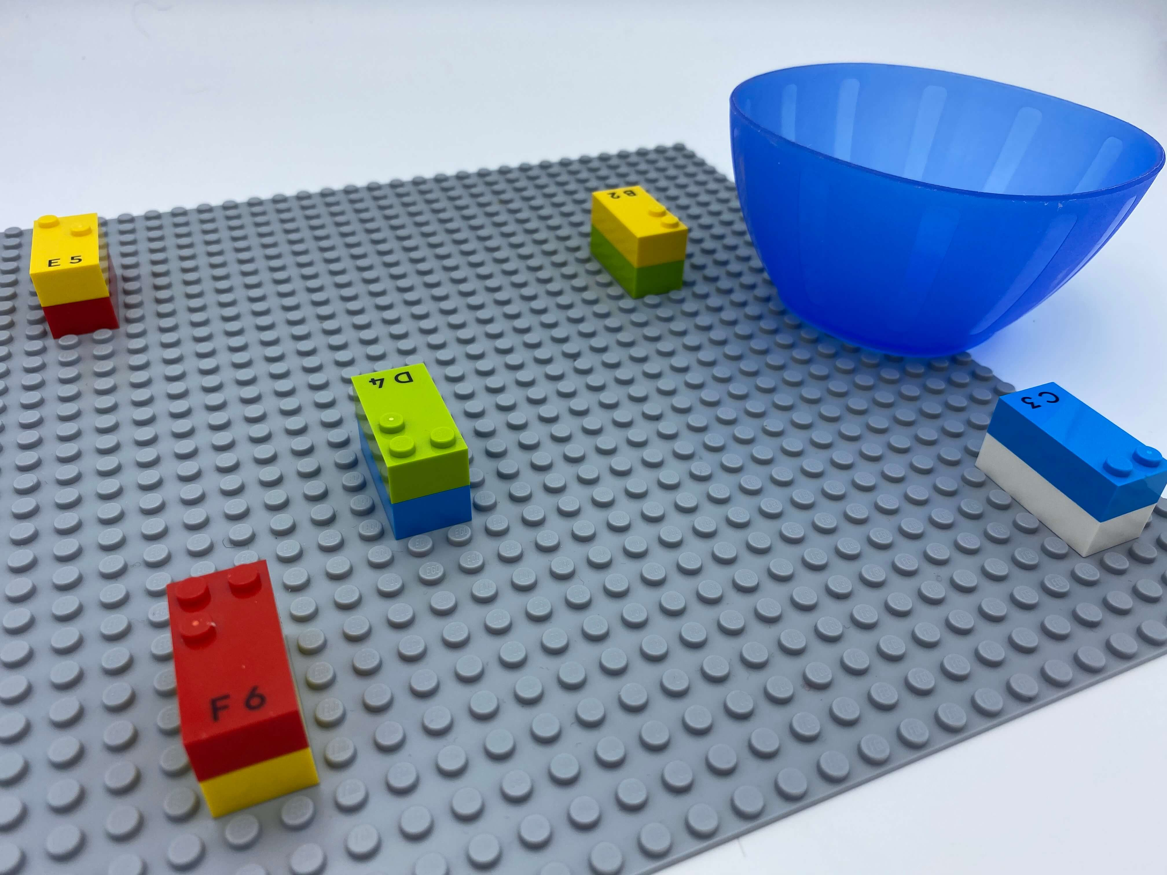 5 bricks covered by another one, spread over the base plate, an empty bowl.
