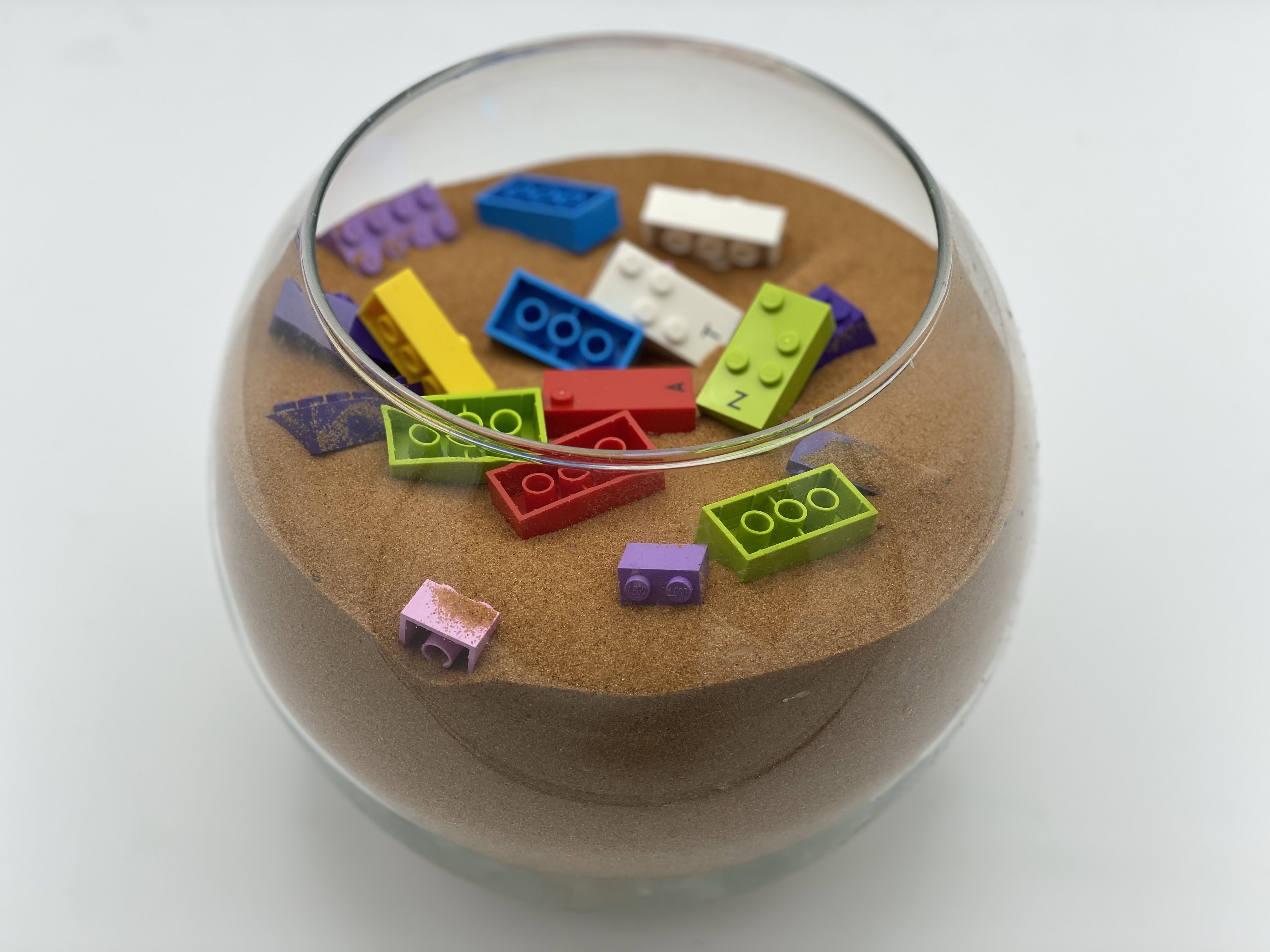 Bricks are places in a round glass aquarium, filled with sand.