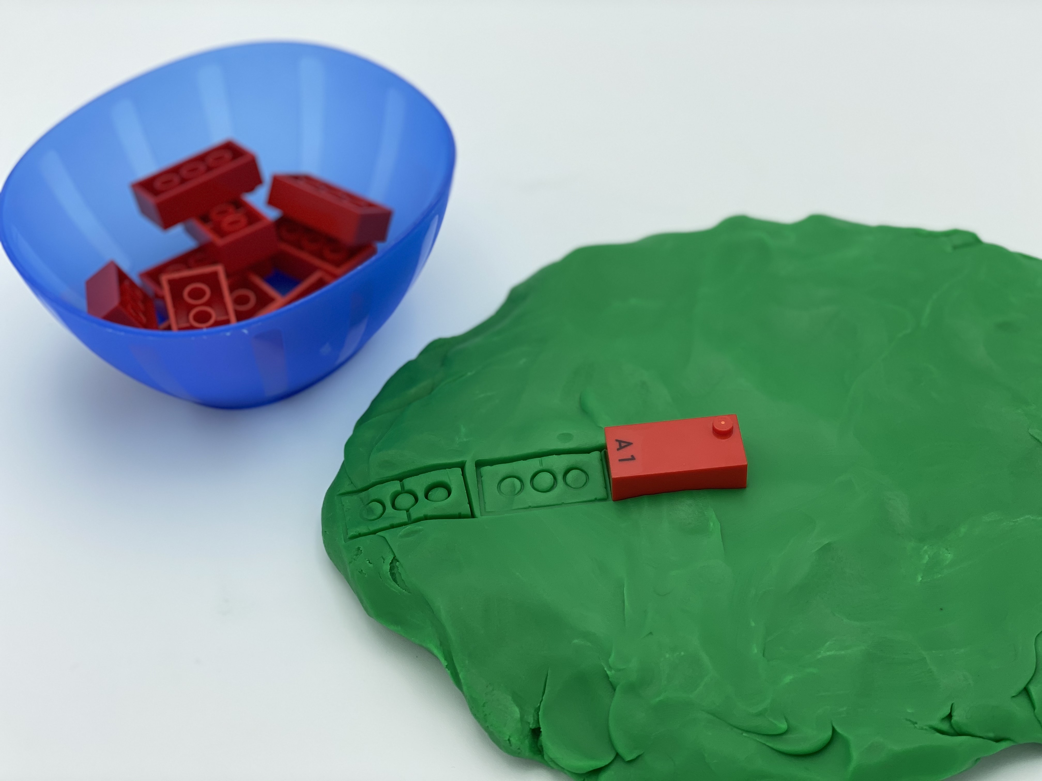"A disk of playdough, prints with an ""a"" brick, a bowl with ""a"" bricks."