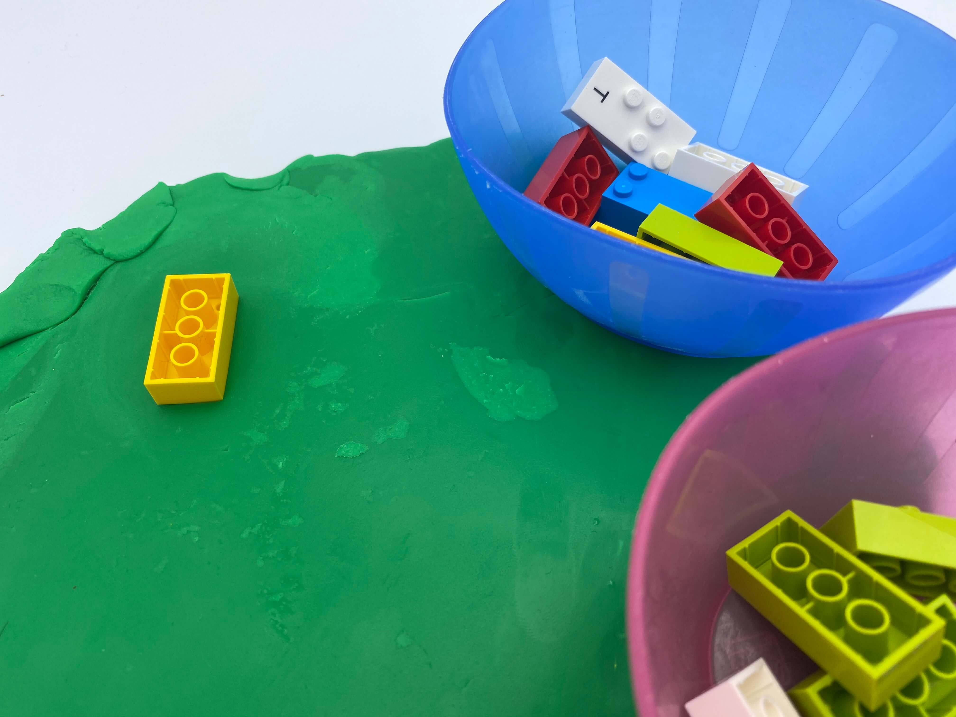 A brick upside down on a flat piece of Play-dough, 2 bowls with bricks inside.
