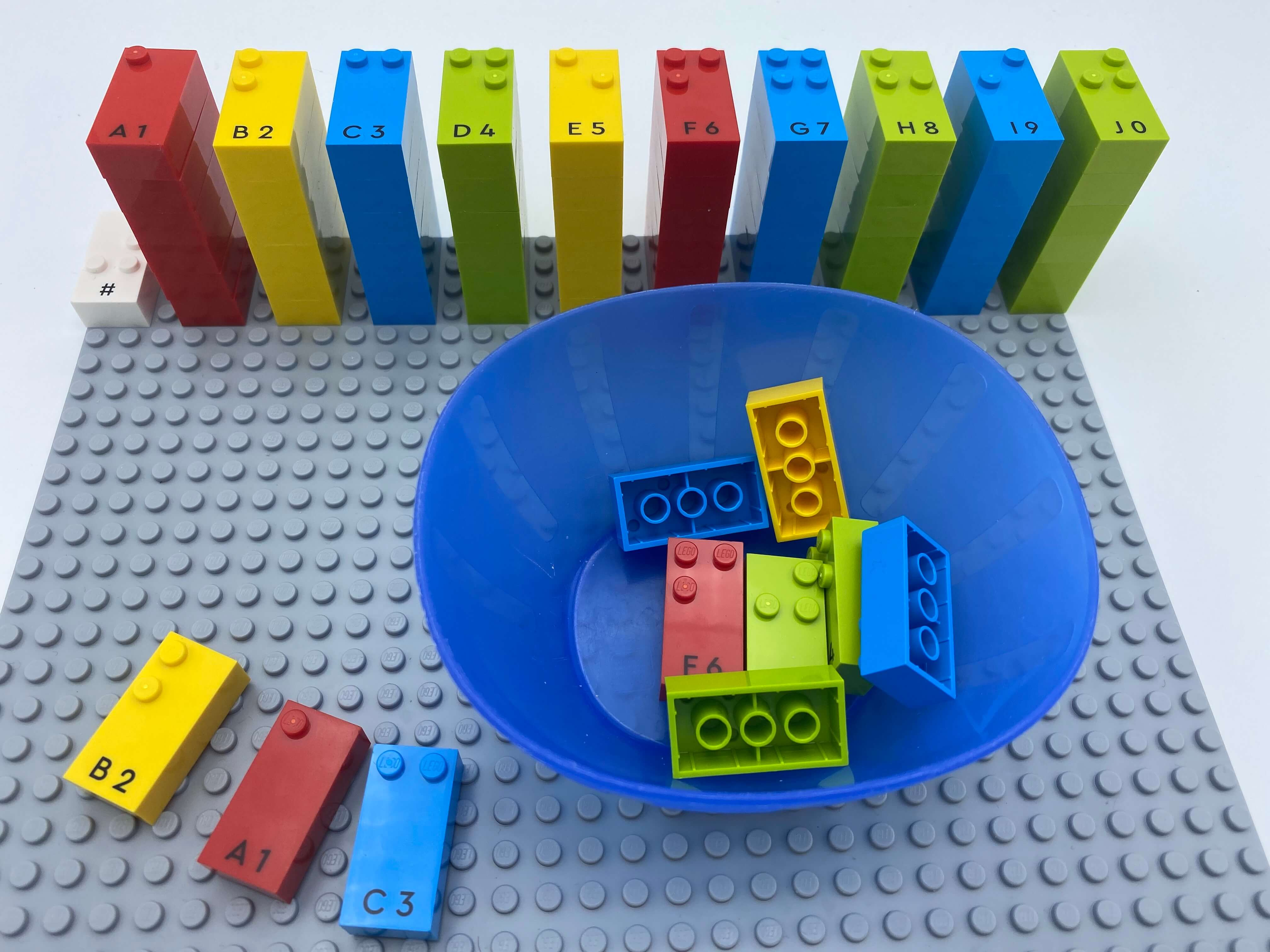 Numbers sign brick and 10 towers of number bricks aligned on the base plate. a bowl with bricks and 3 number bricks out of the bowl: 2, 1, 3.