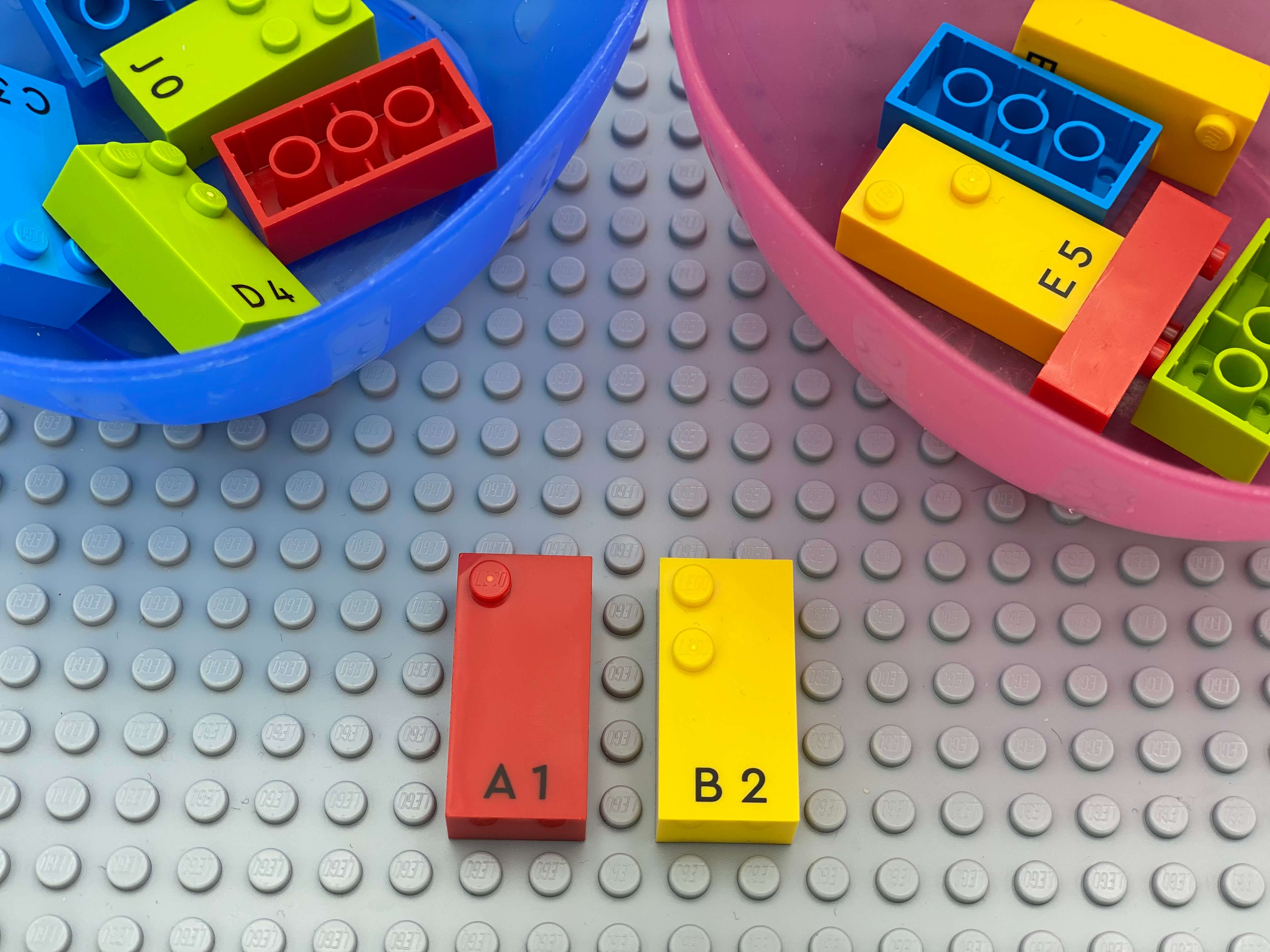 Letter bricks b and a aligned on the base plate, 2 bowl with bricks.