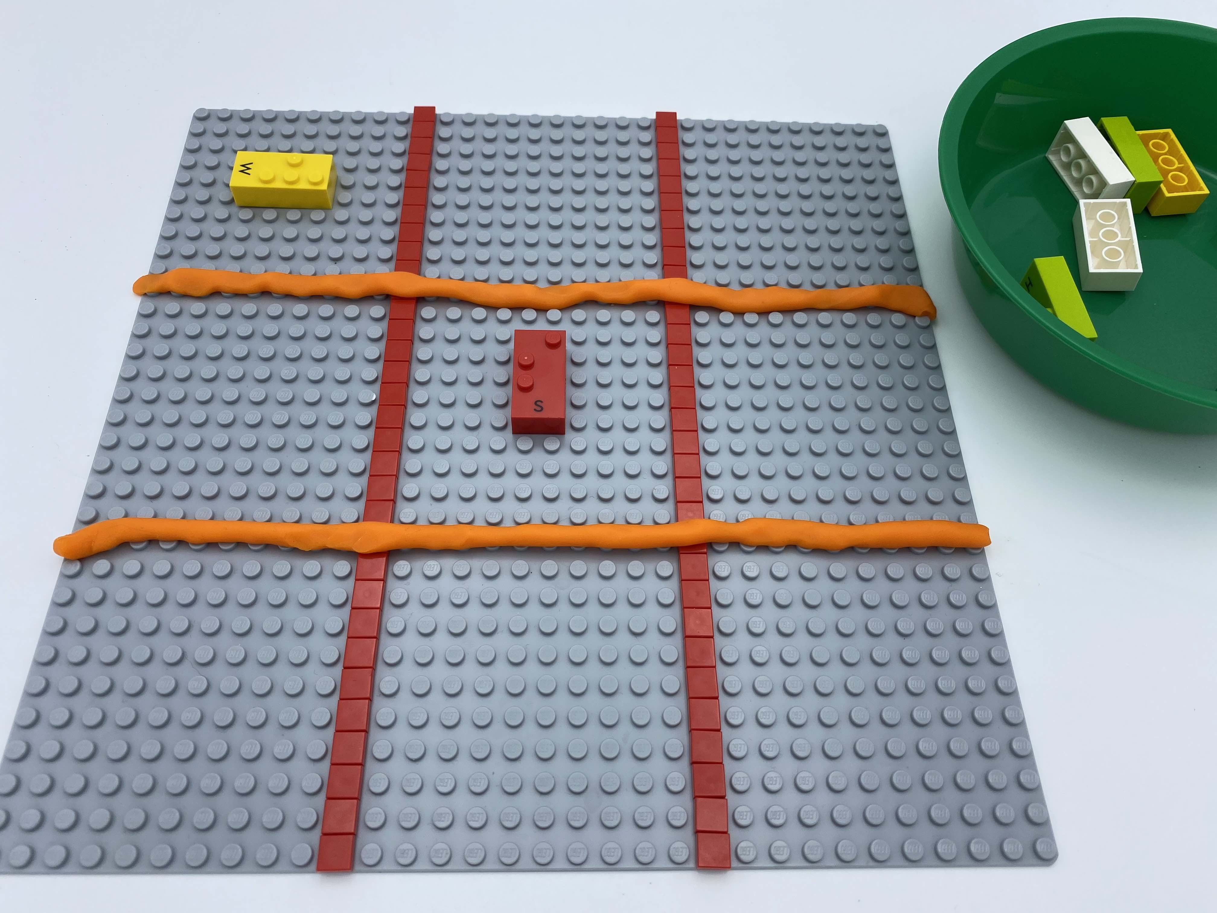 9 squares on a base plate. A horizontal bricks in top left square, a vertical brick in the middle one.