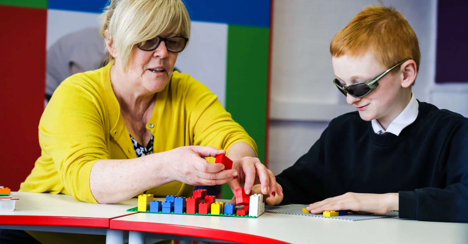 Teacher and child using LEGO Braille Bricks