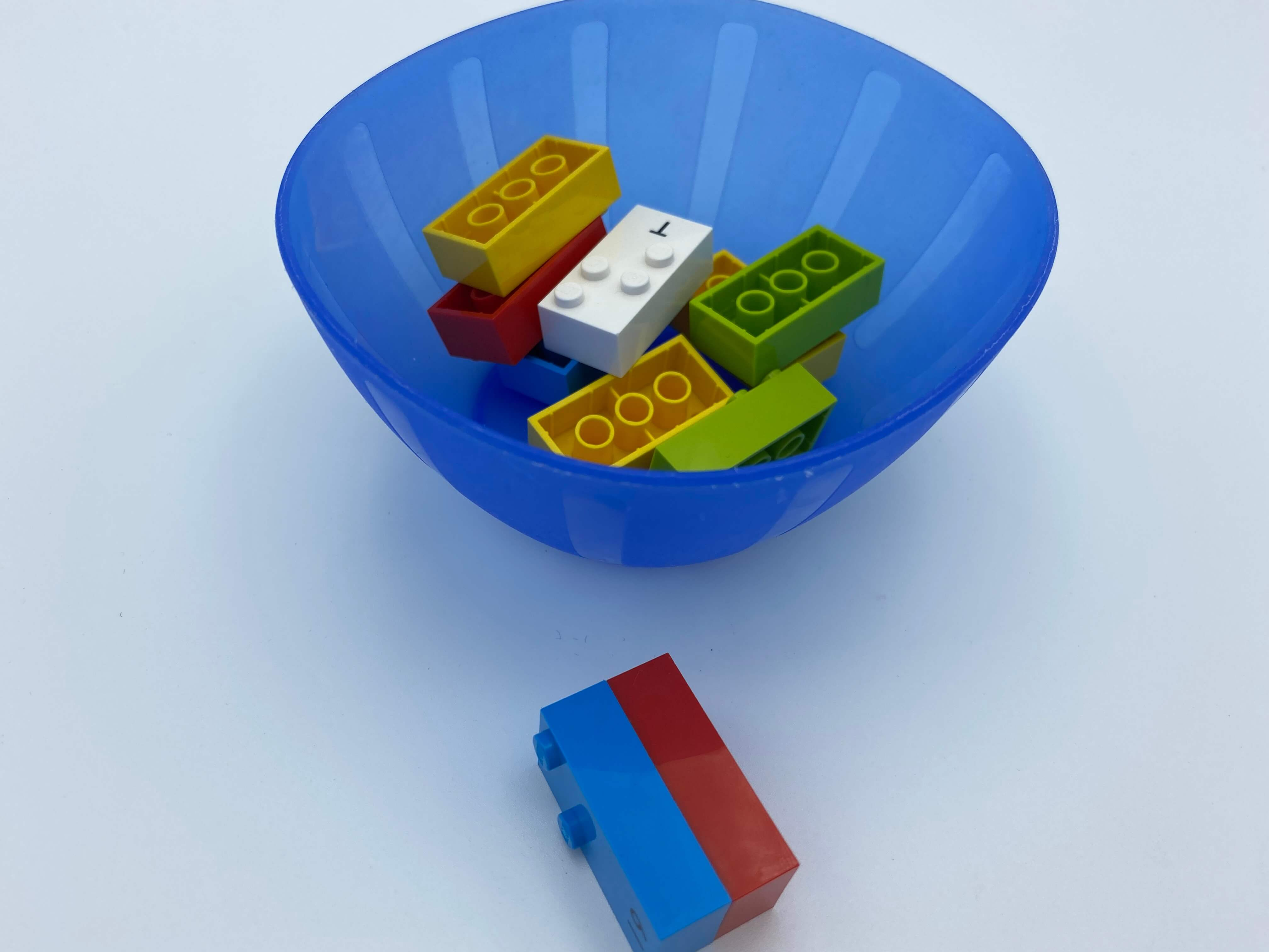 2 bricks attached, on a table, a bowl with 8 bricks.