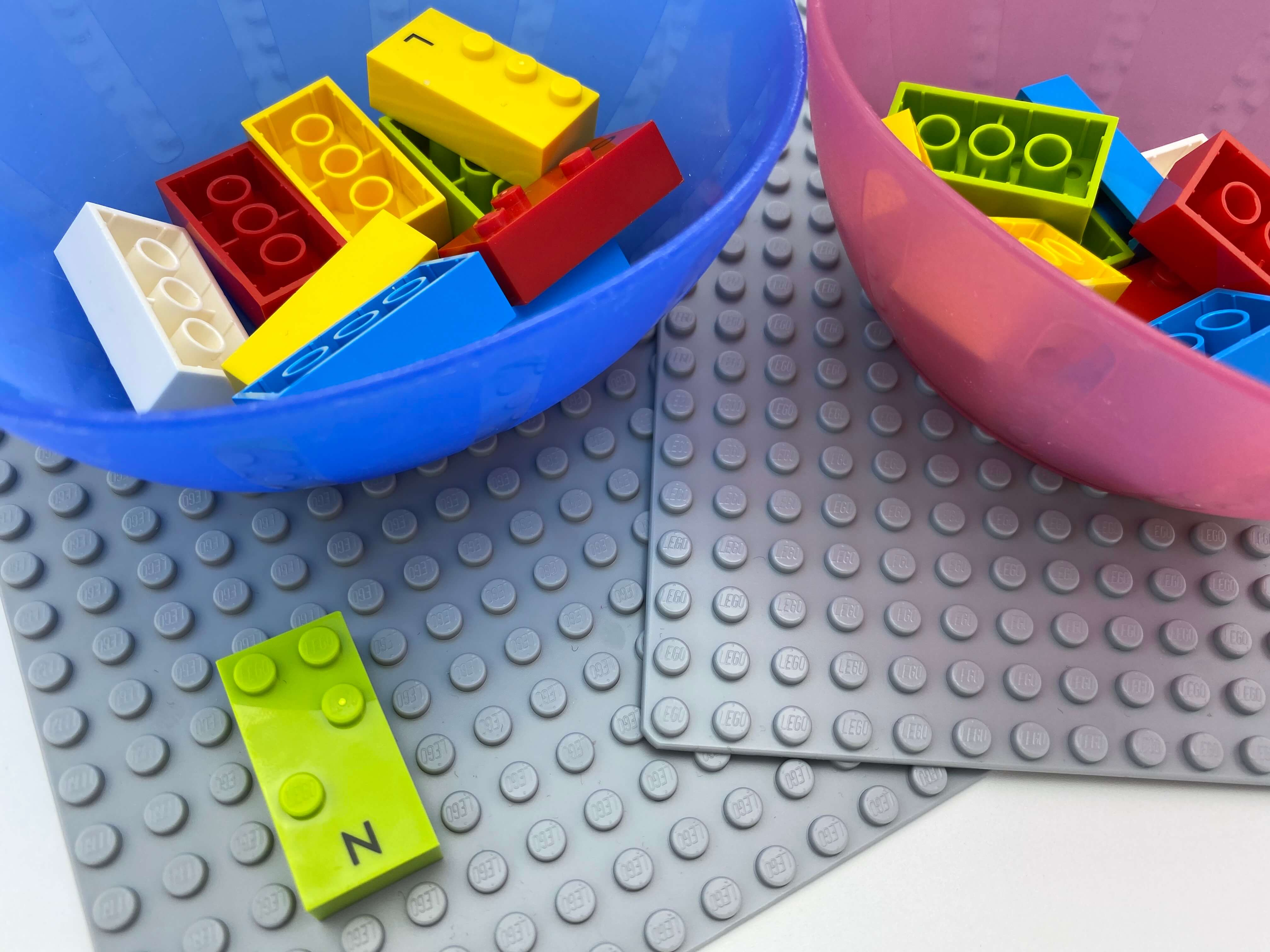 """2 base plates, 2 bowl with bricks. A letter brick """"n"""" on one base plate."""
