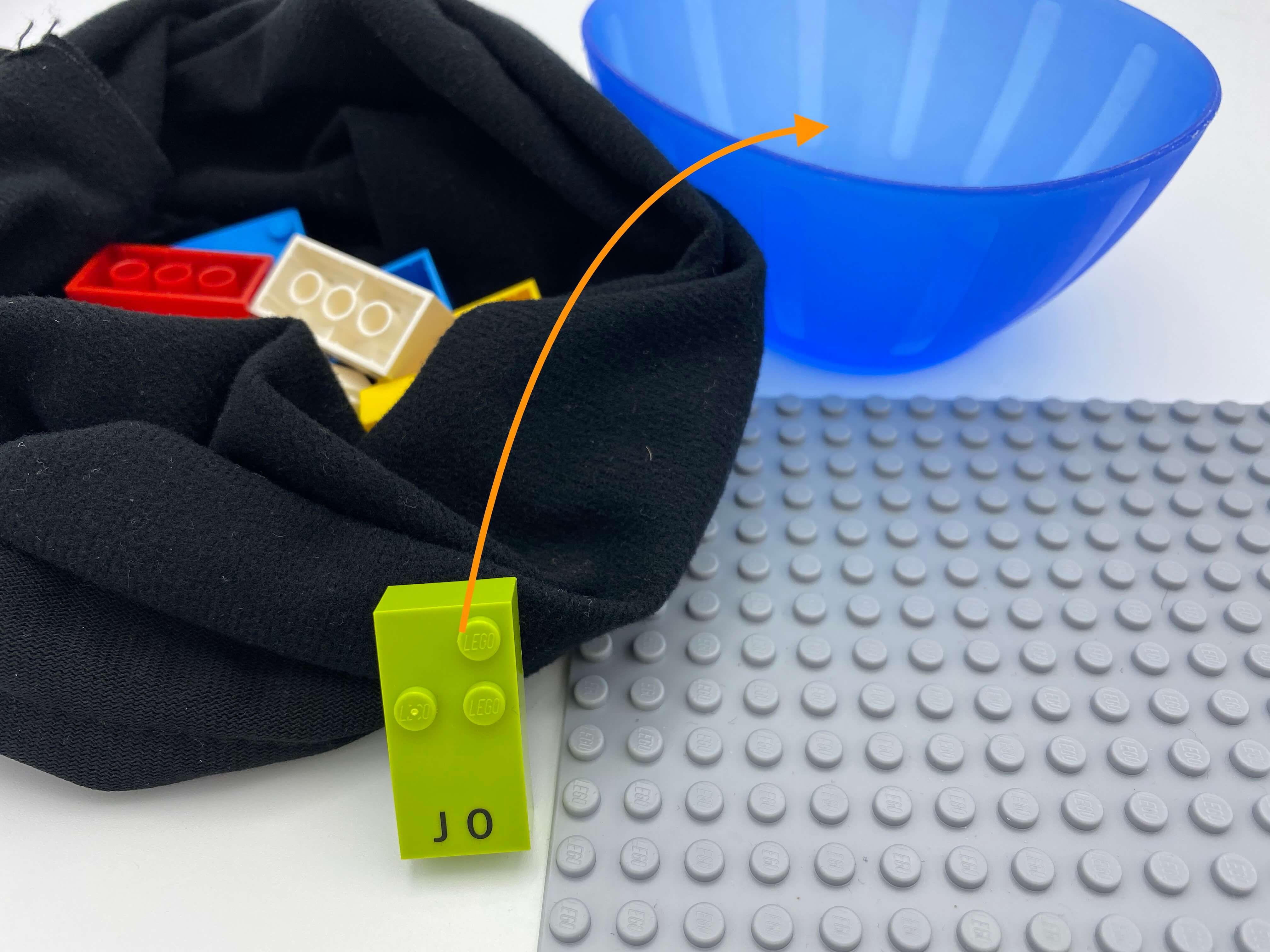 A bag full of bricks, letter brick j being placed in the empty bowl.
