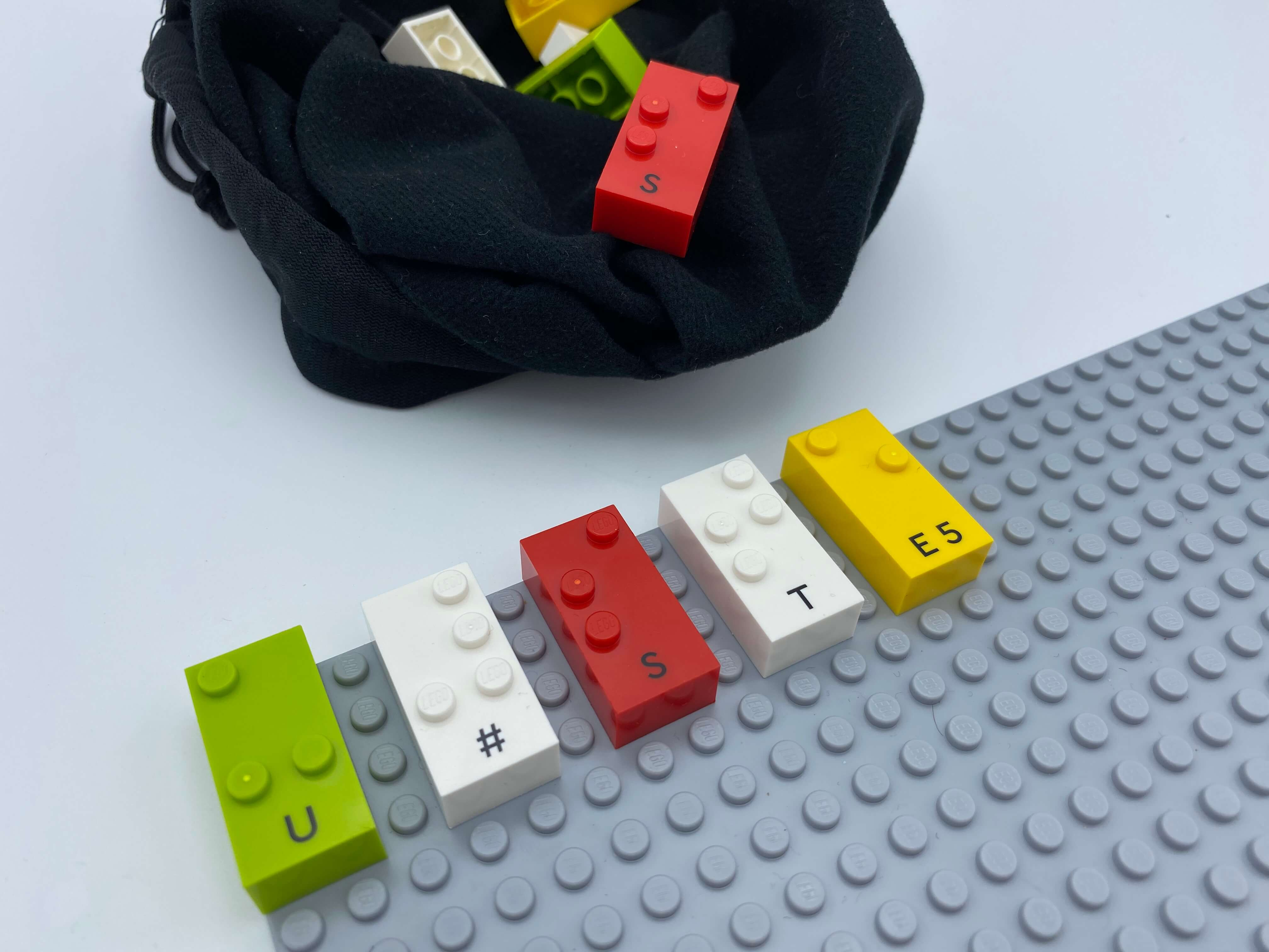 Bricks u, #, s, t, e aligned on the base plate, a bag with exact same set of letters hidden.