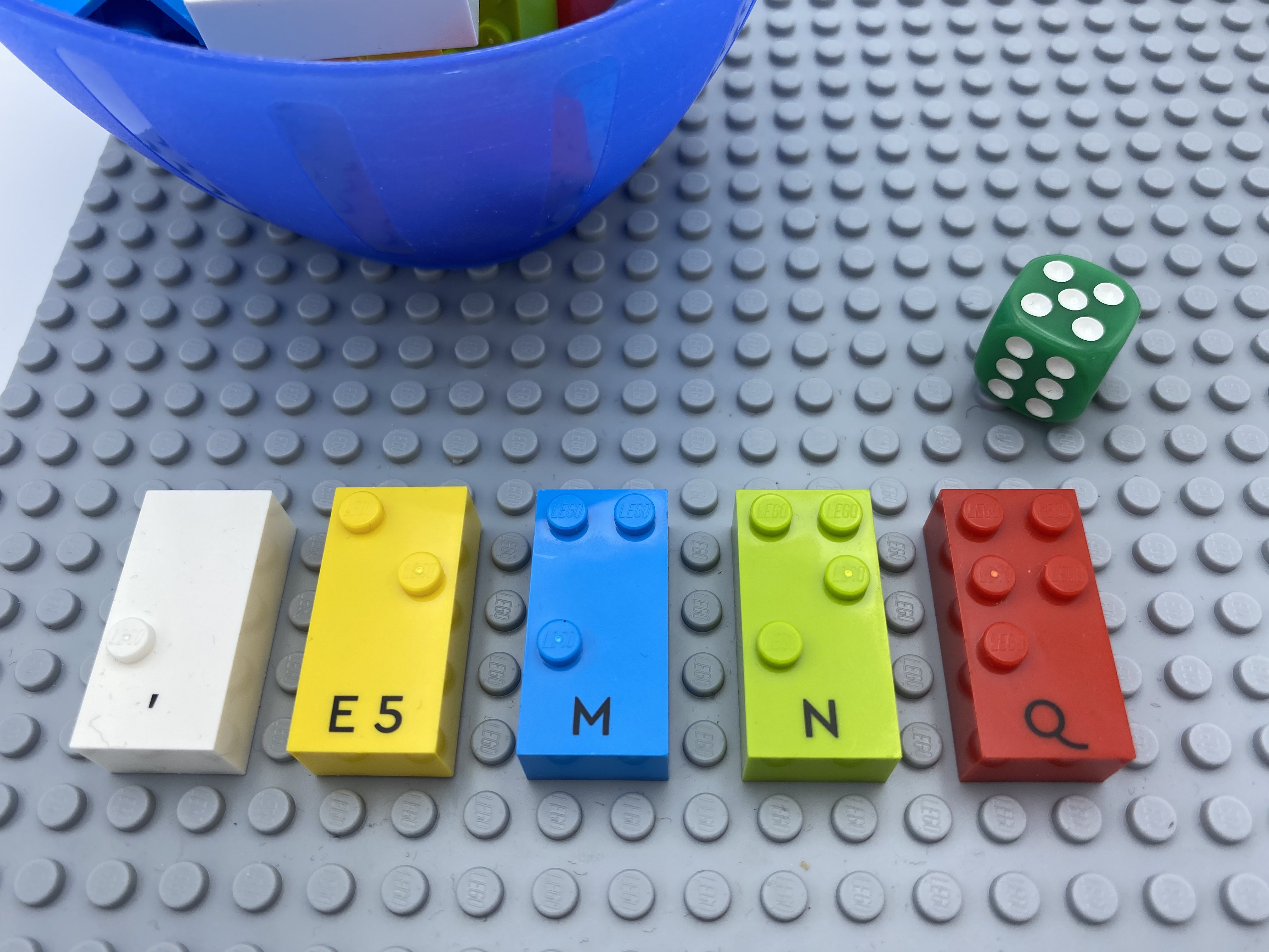 "die roll = 5, letter brick Q. All five categories of bricks on the base plate: "","",  ""e"",  ""m"", ""n"" and ""q""."