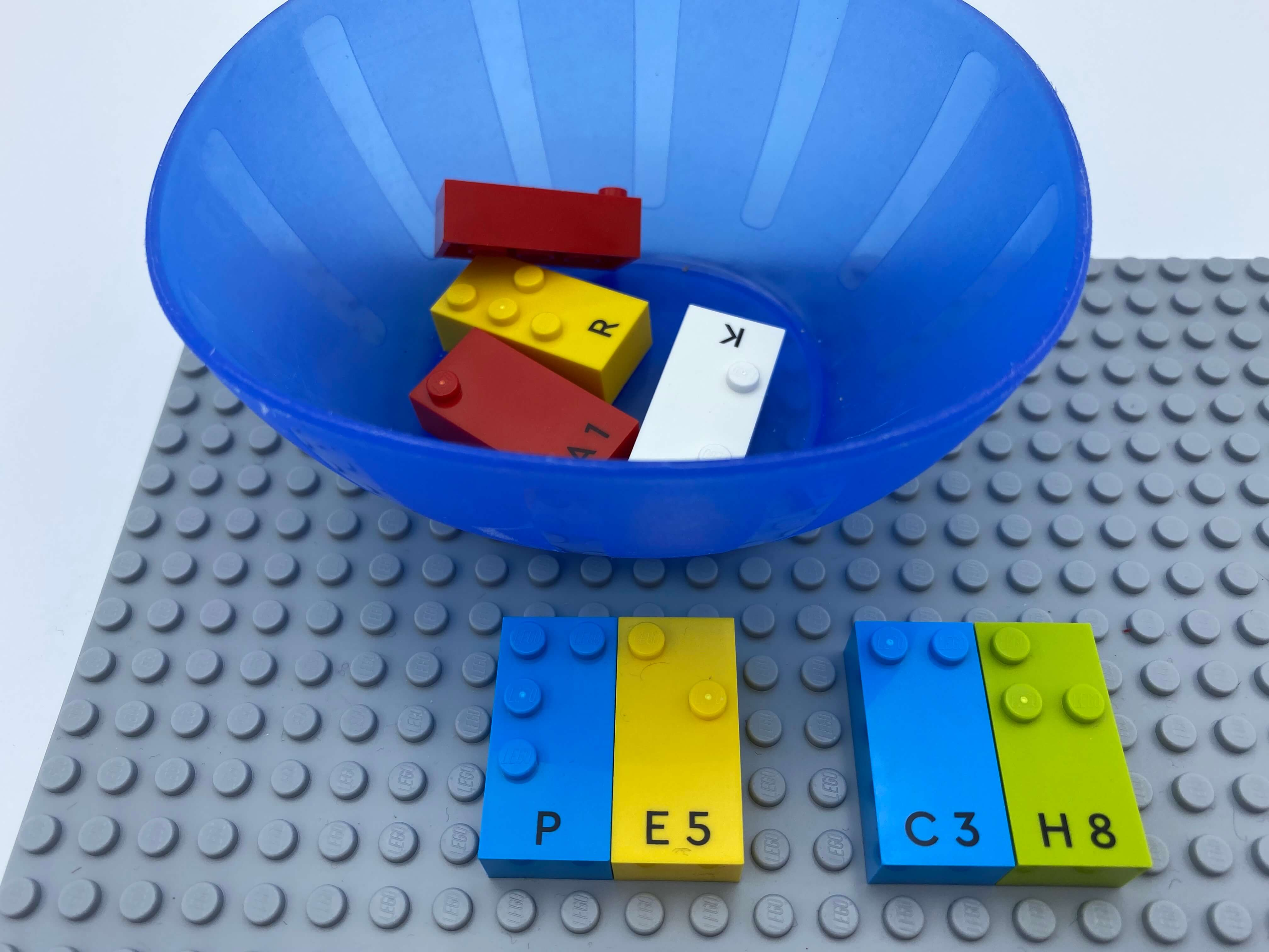 2 pairs of letter bricks (p, e and c, h) aligned on the base plate, a bowl with bricks.