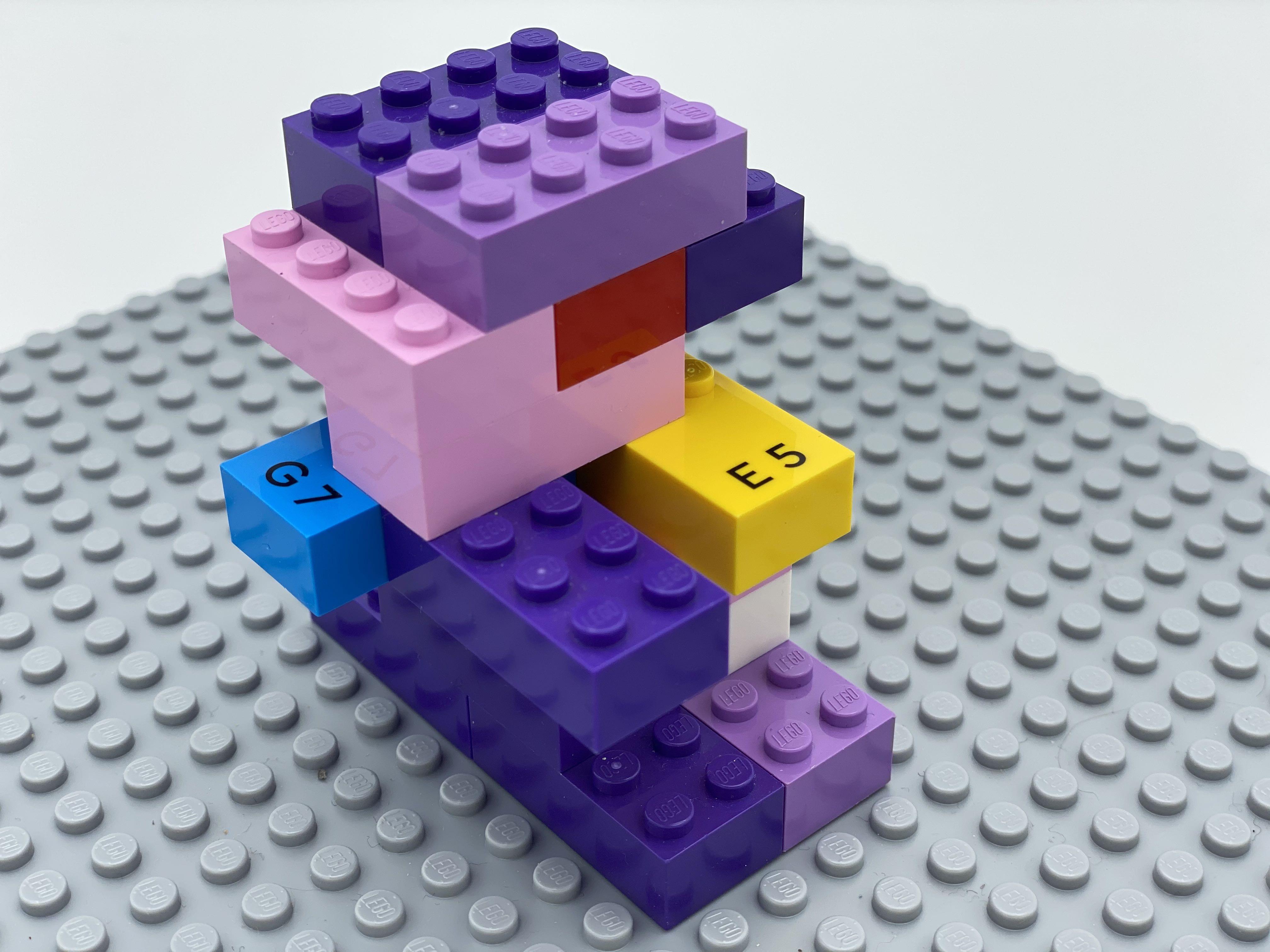 Letter bricks g, a, t, e hidden in a construction made of standard 2x4 LEGO bricks.