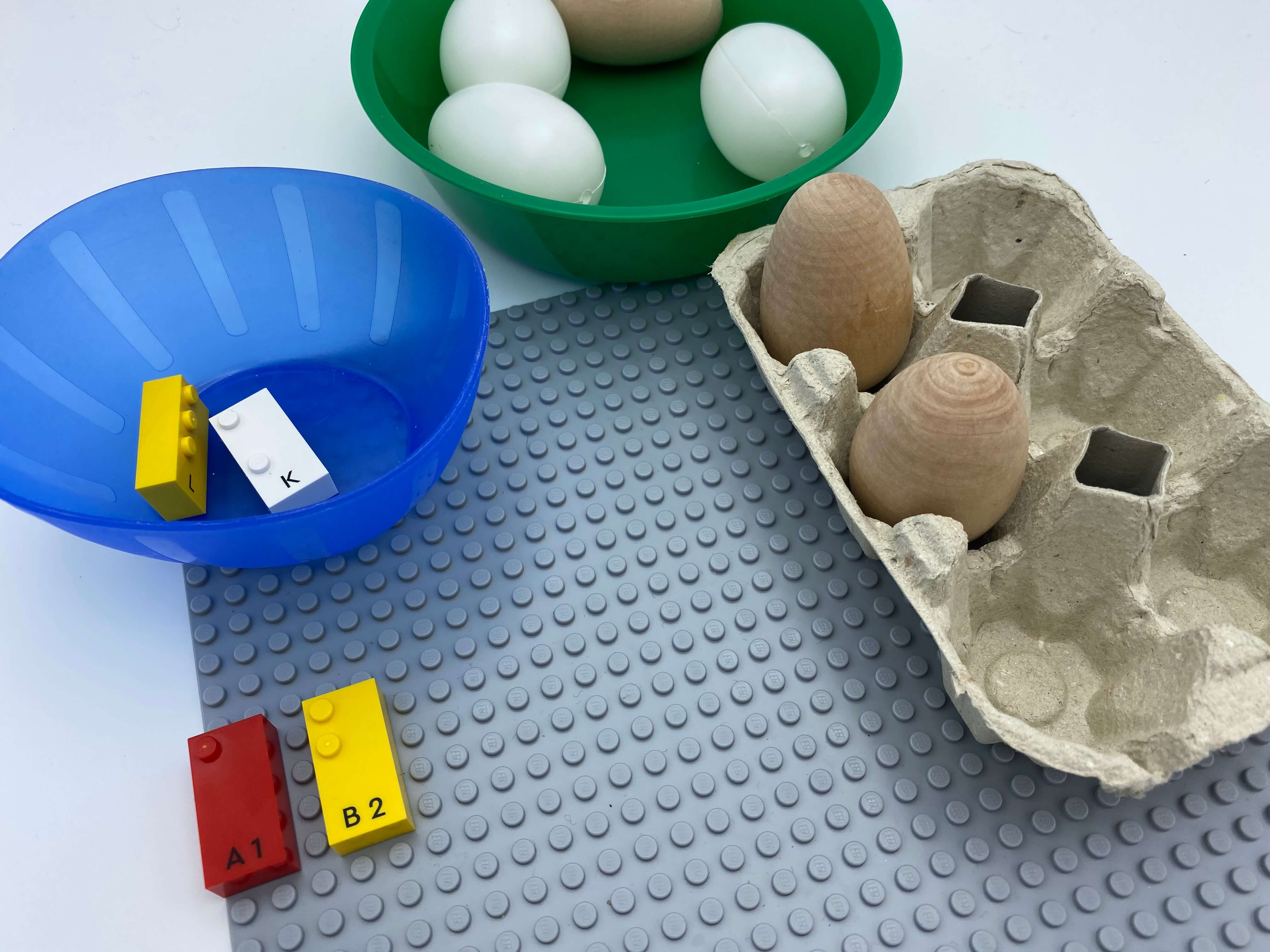 Letter brick b on the base plate, egg carton with 1 egg in dot 1 and in dot 2.