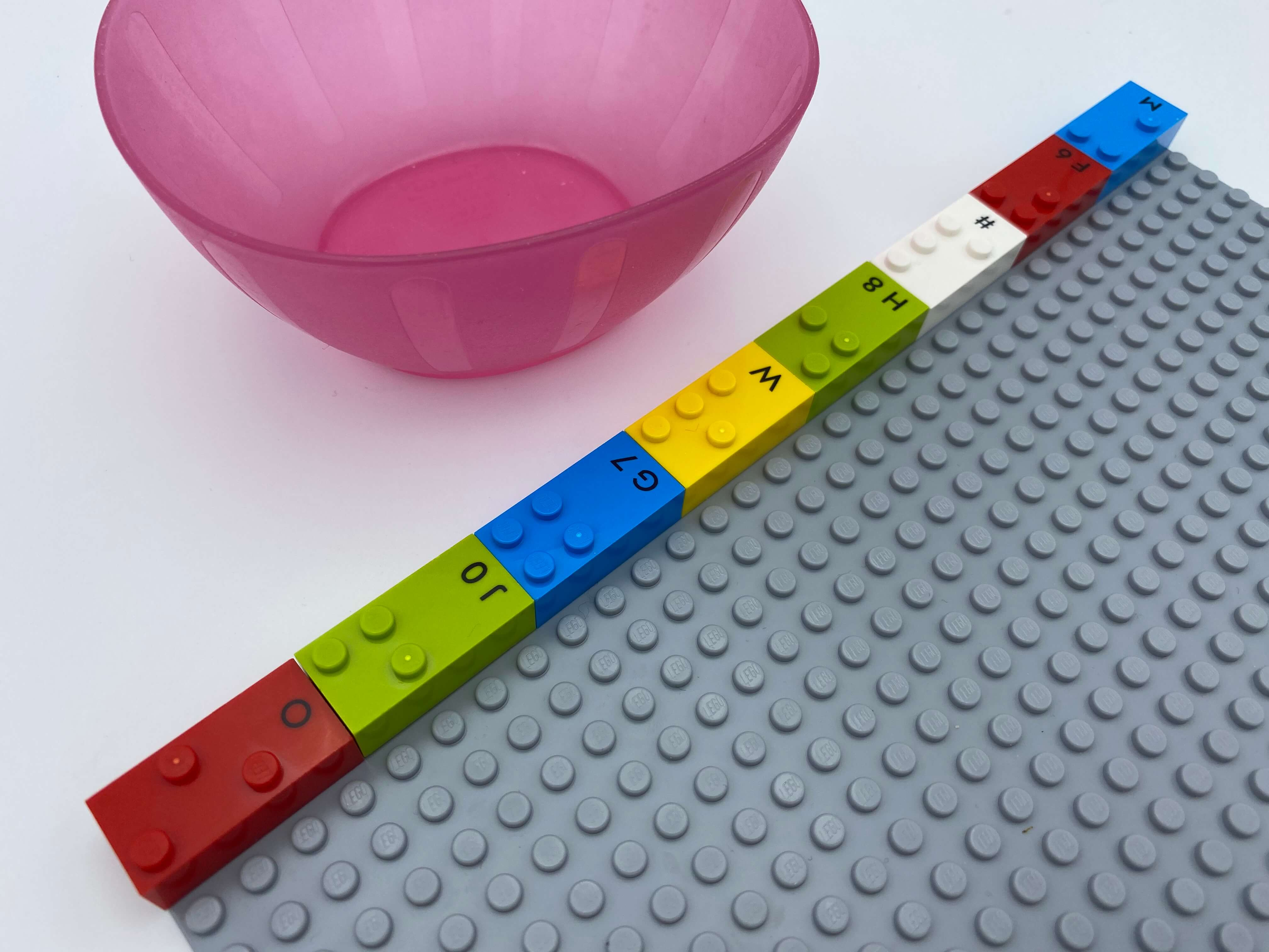 A horizontal row of 8 horizontal bricks on top of the base plate, an empty bowl.