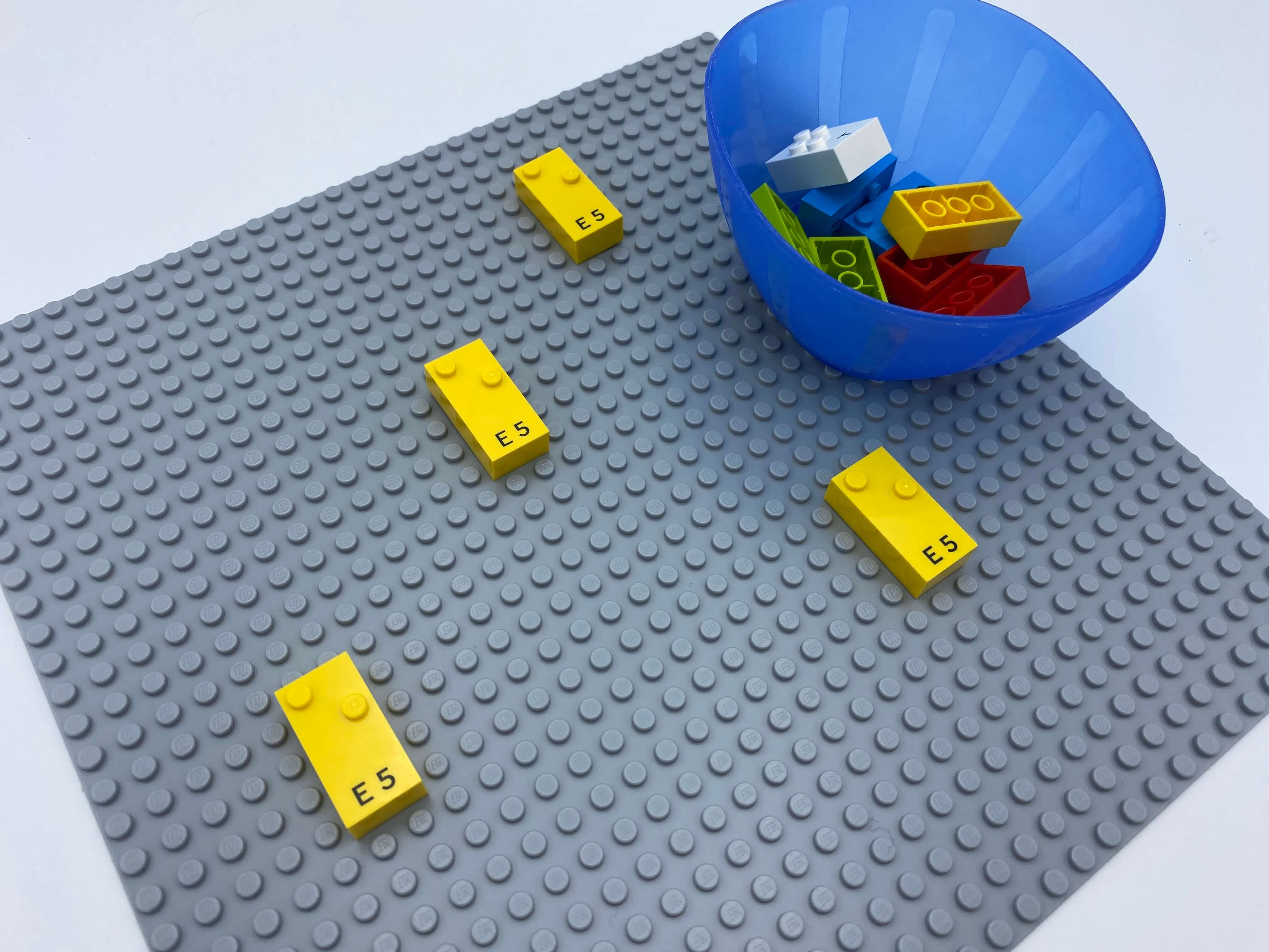 4 letter bricks spread over the base plate, one bowl with bricks.