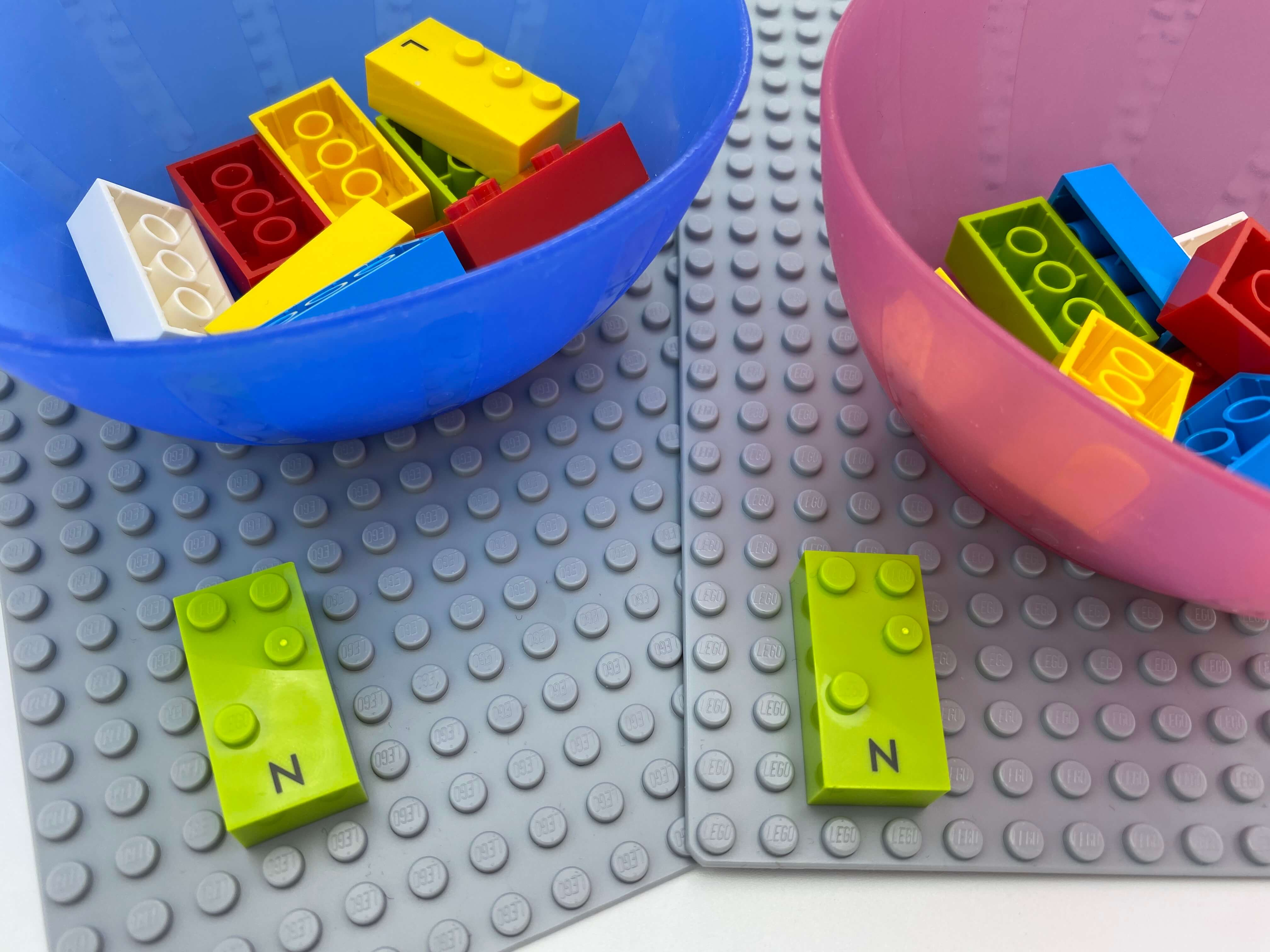 """2 base plates with a letter brick """"n"""" on each , 2 bowl with bricks."""