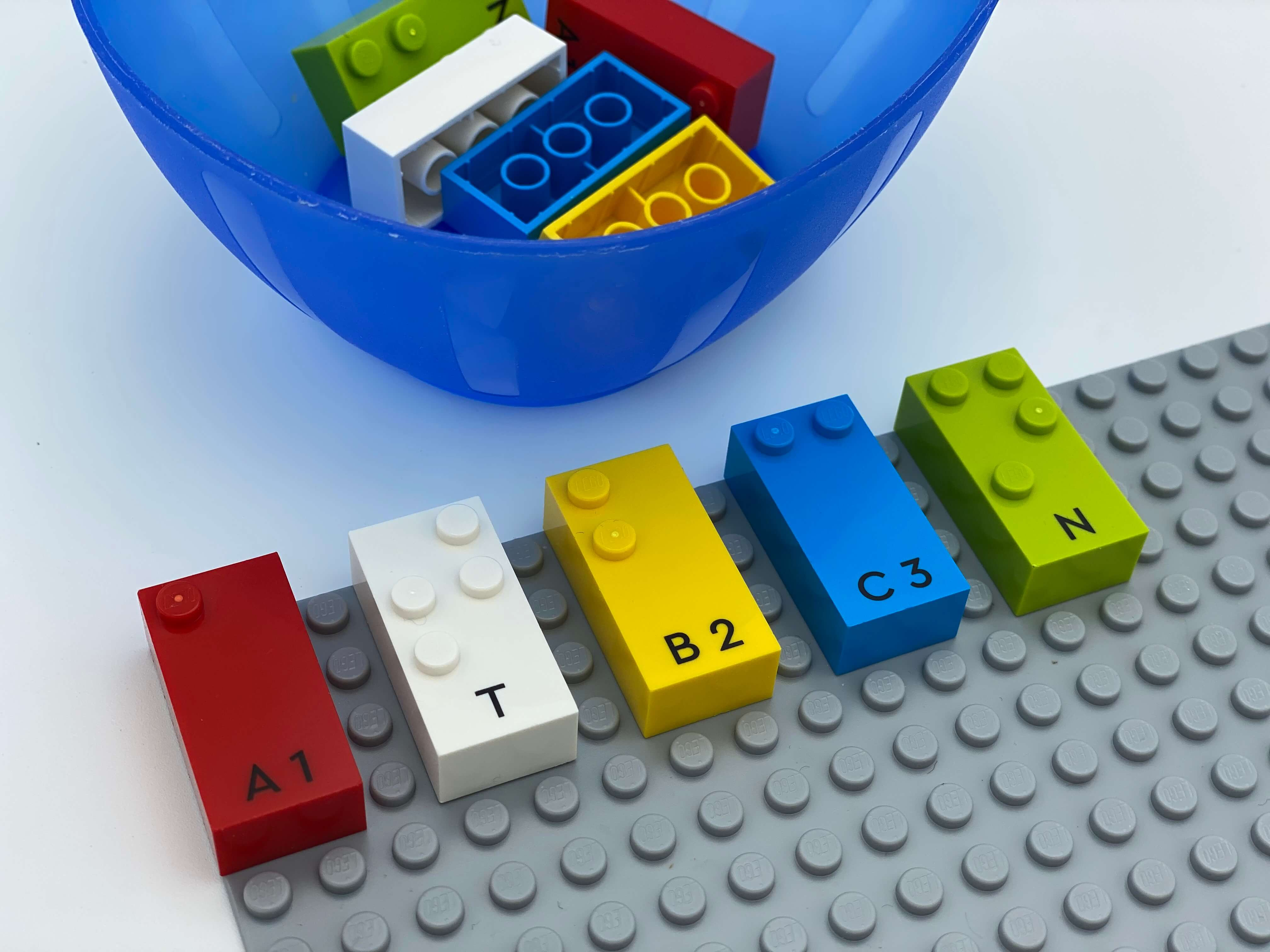 5 letter bricks aligned on the base plate: a, t, b, c, n. A bowl with bricks.