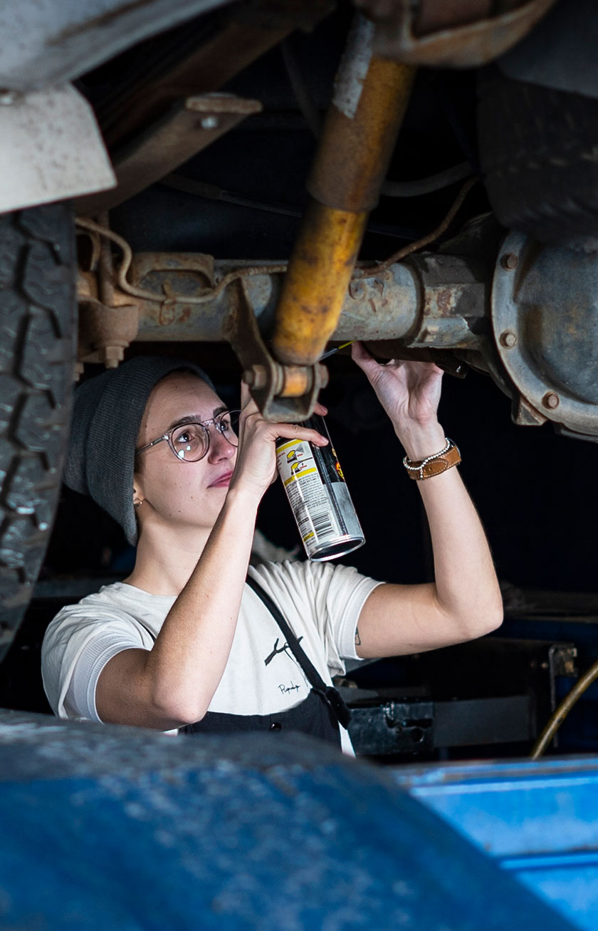 CaseStudy WD40 Image6 | A mechanic applies a WD-40 product to a lifted vehicle's axle.