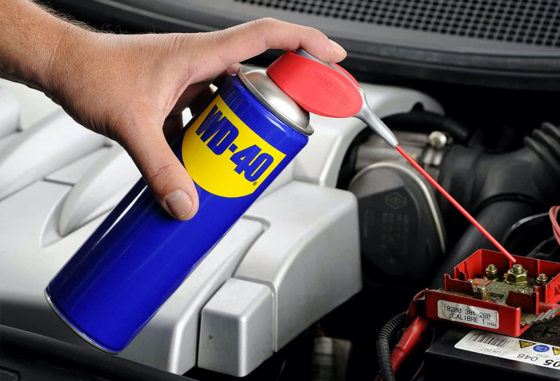 CaseStudy WD40 Image1 | A hand applying WD-40 from a can to a mechanical component of some kind.
