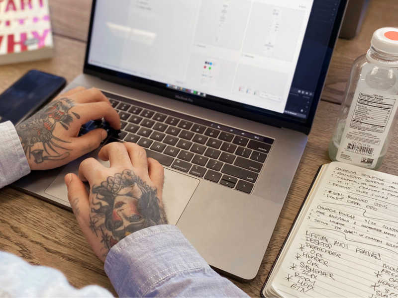 Hands with cool tattoos at a laptop.