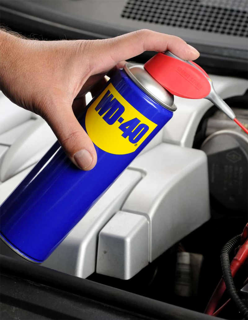 A hand applying a WD-40 product to a mechanism.