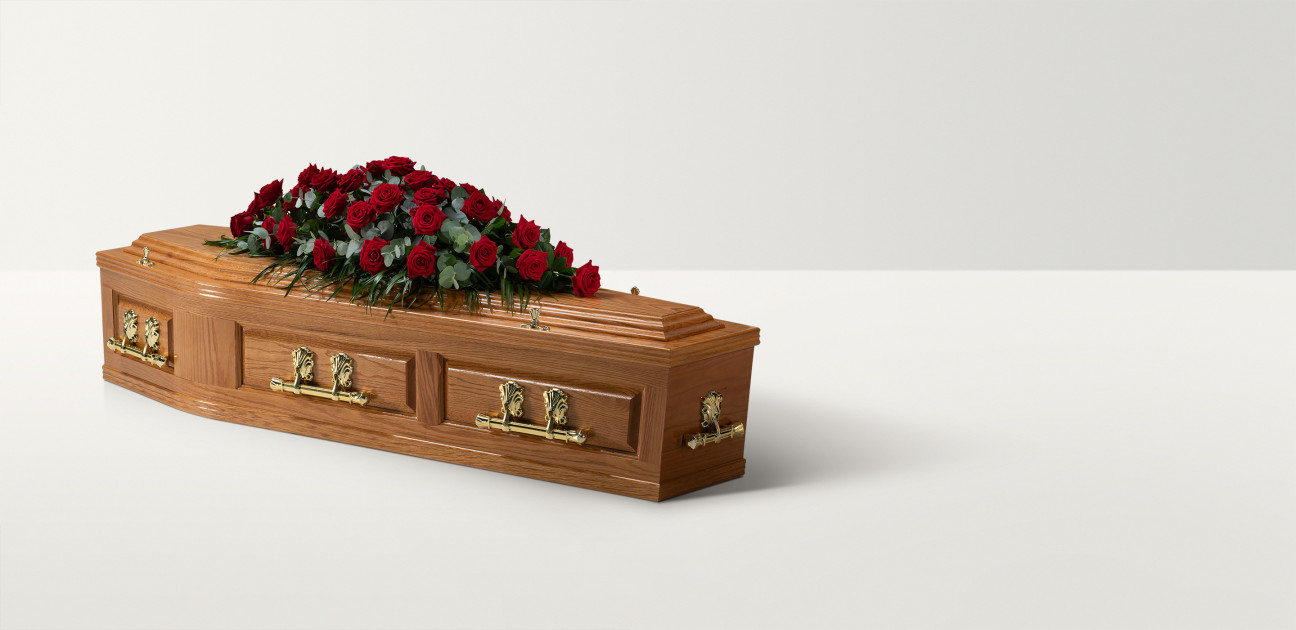 Pannelled oak coffin with rose floral arrangement on top