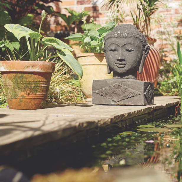 Stone buddha head on a stand in a garden next to a pond