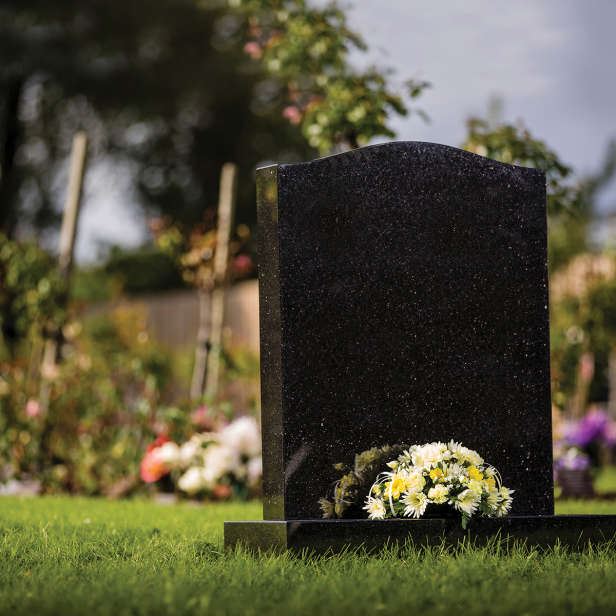 Black headstone with a white and yellow floral arrangement in a garden
