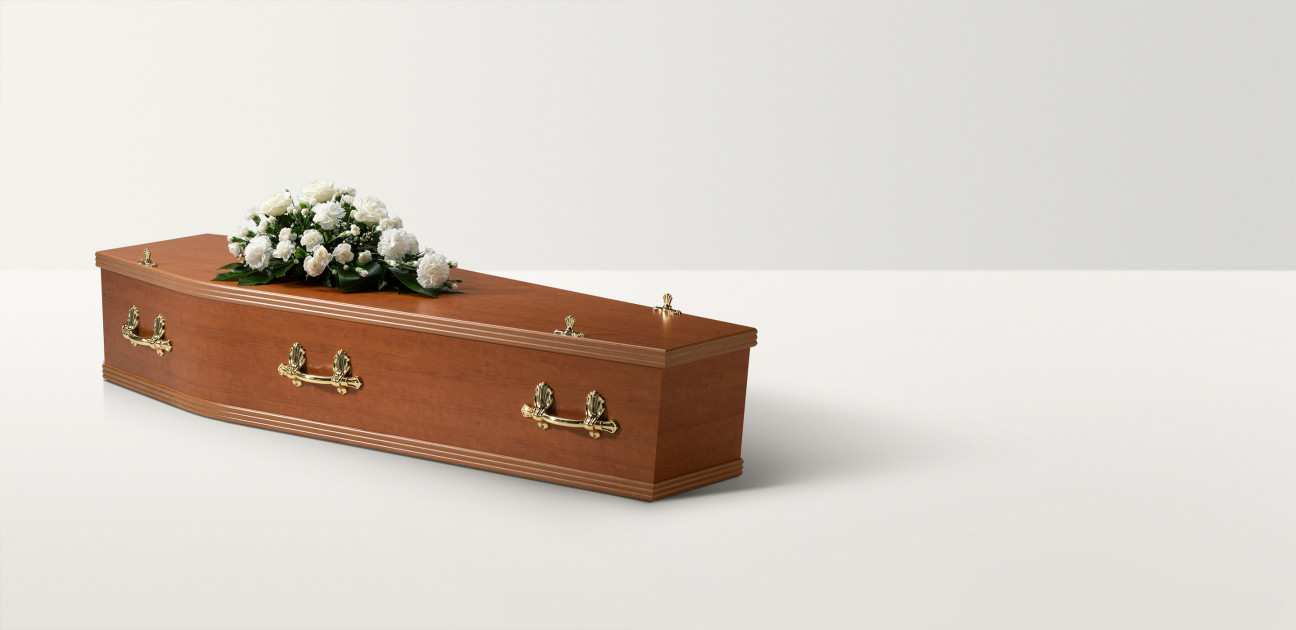 Cherry wood coffin with white rose floral arrangement