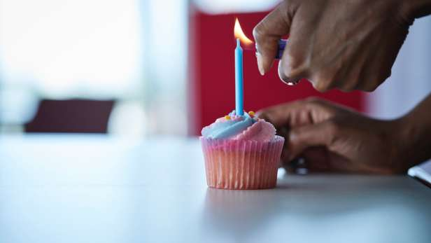 Person lighting a candle in a single cup cake.