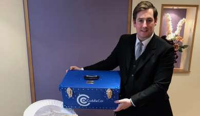 Funeral director holding a cuddle cot.