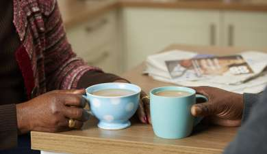 Couple chatting in their kitchen over a cup of tea.