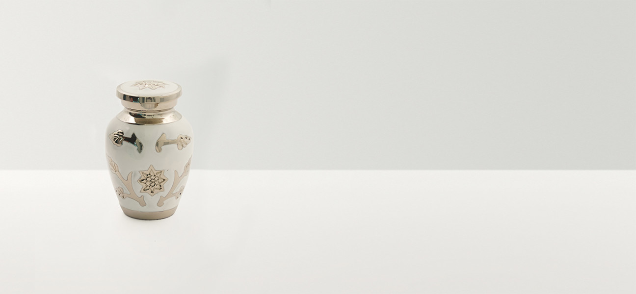 White urn with silver flower decoration