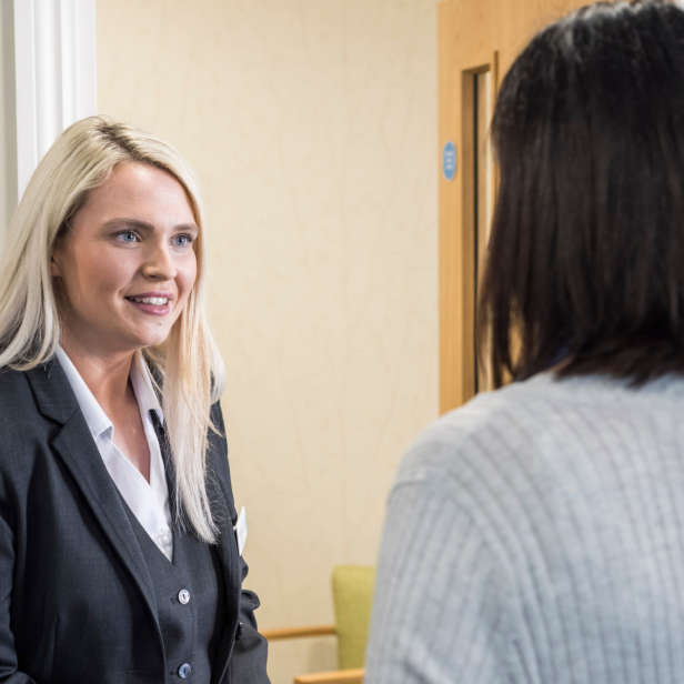 Blonde person in a suit talking to a dark haired person with a light top