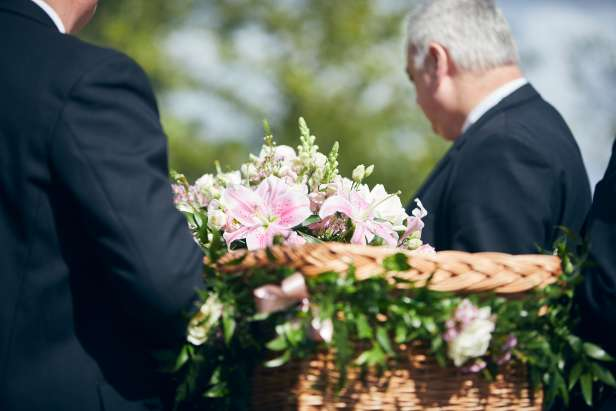 Coffin topped with flowers being carried
