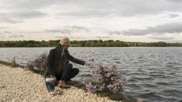 Woman scattering ashes next to a lake