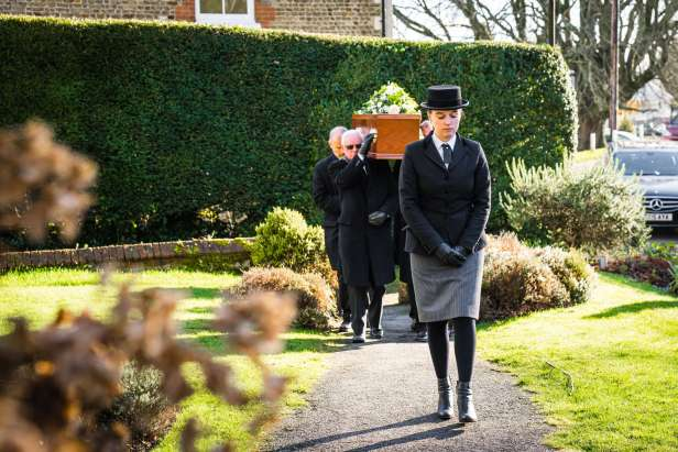 Pallbearers processing with a coffin up a path in a garden
