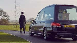 Funeral director leading a funeral procession.