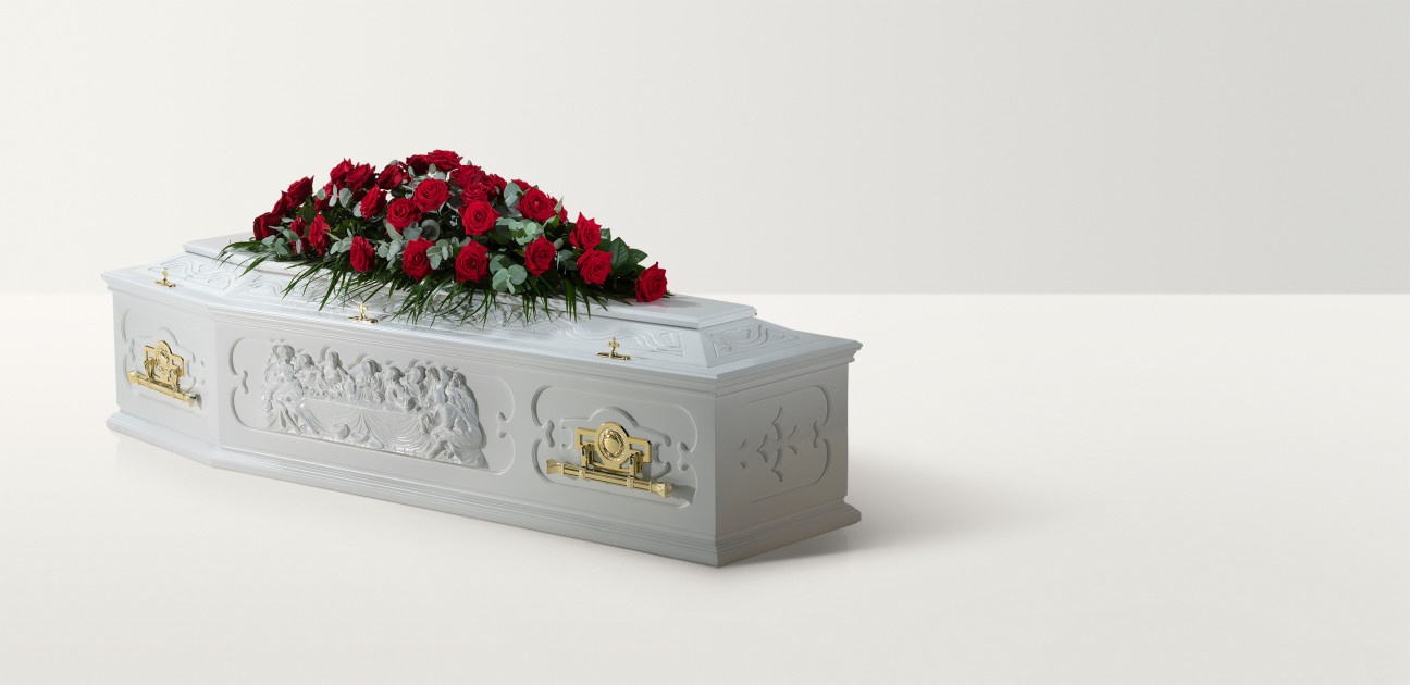White coffin with a depiction of the last supper and large rose floral arrangement on top