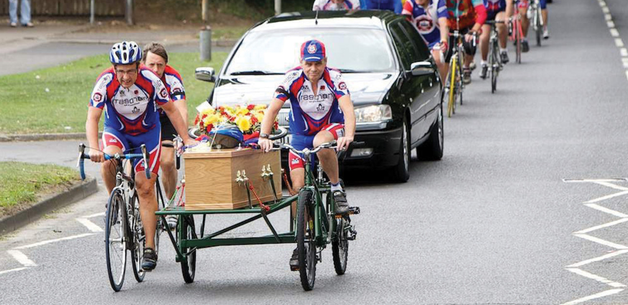 Funeral procession with a coffin with helmet and floral arrangement on a hearse pulled by bicycles