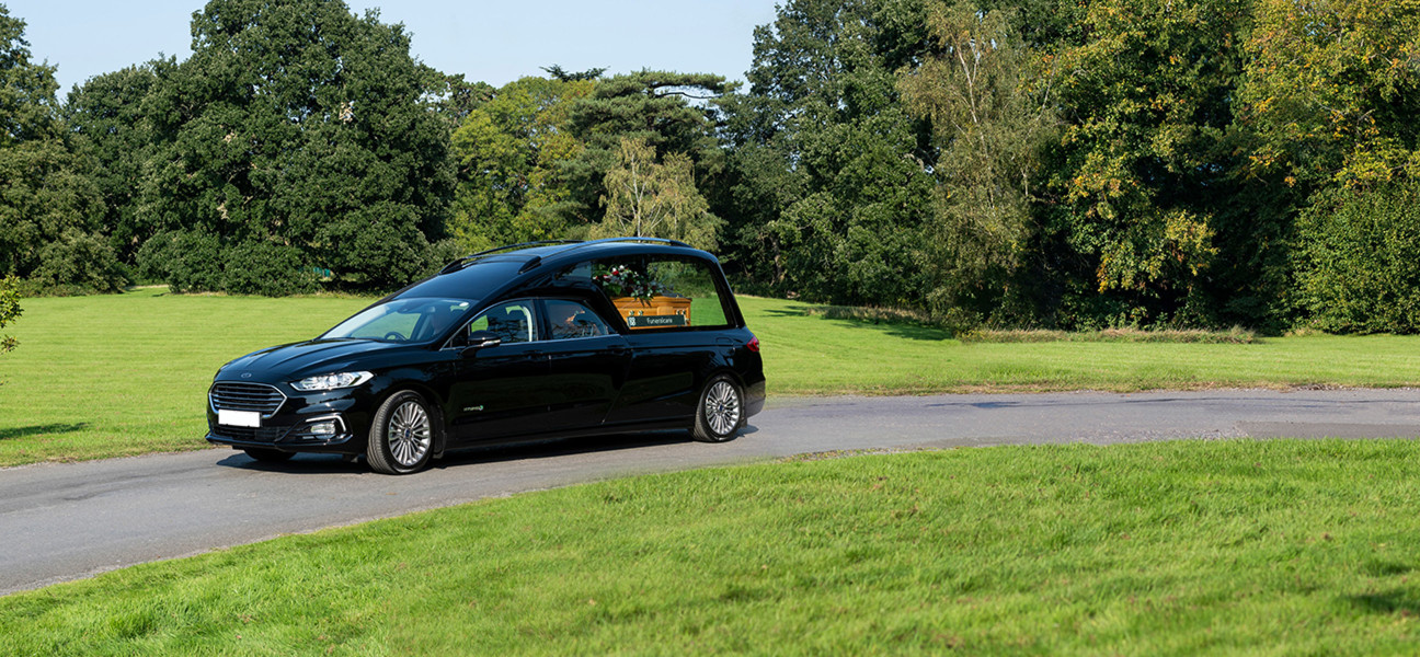 Black hearse with a coffin inside driving through a green parkland
