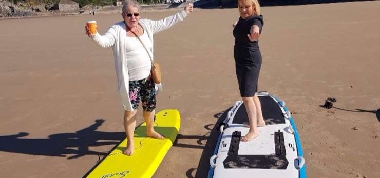 Two members of the bereavement group on surf boards on the beach.