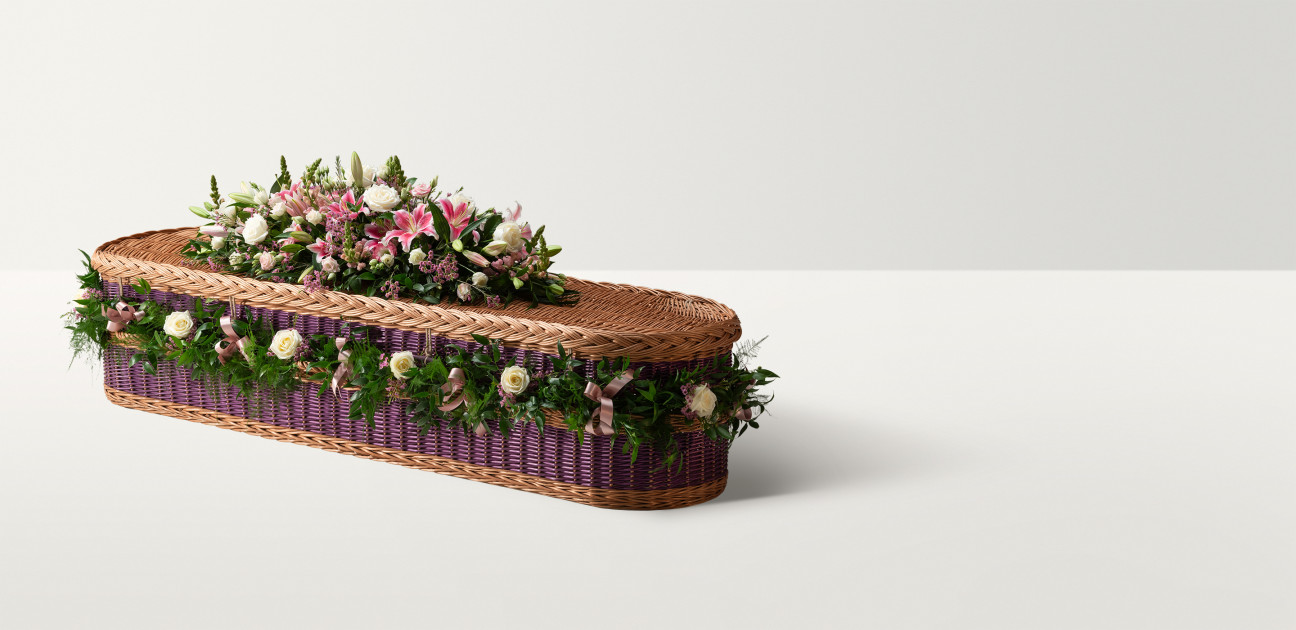 Heritage willow coffin in purple and natural willow with a floral garland and bright spray on top