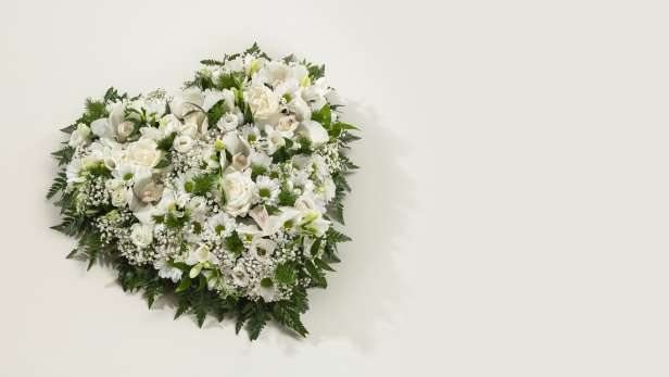 Heart shaped floral arrangement in white on green foliage