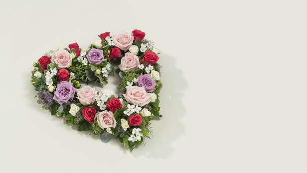 Heart shaped flower arrangement with pink, red and purple roses and white flowers