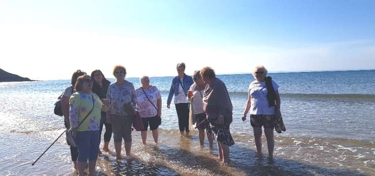 Bereavement group having a paddle in the sea on a summers day.