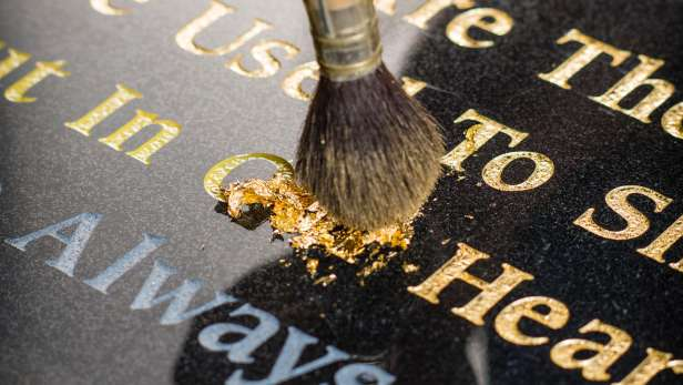 Brushing gold leaf into the engraving on a headstone.