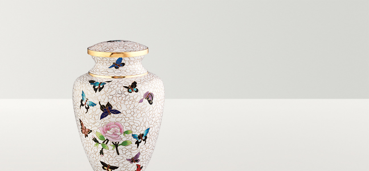 Close up image of a white urn with butterflies and roses and a copper rim