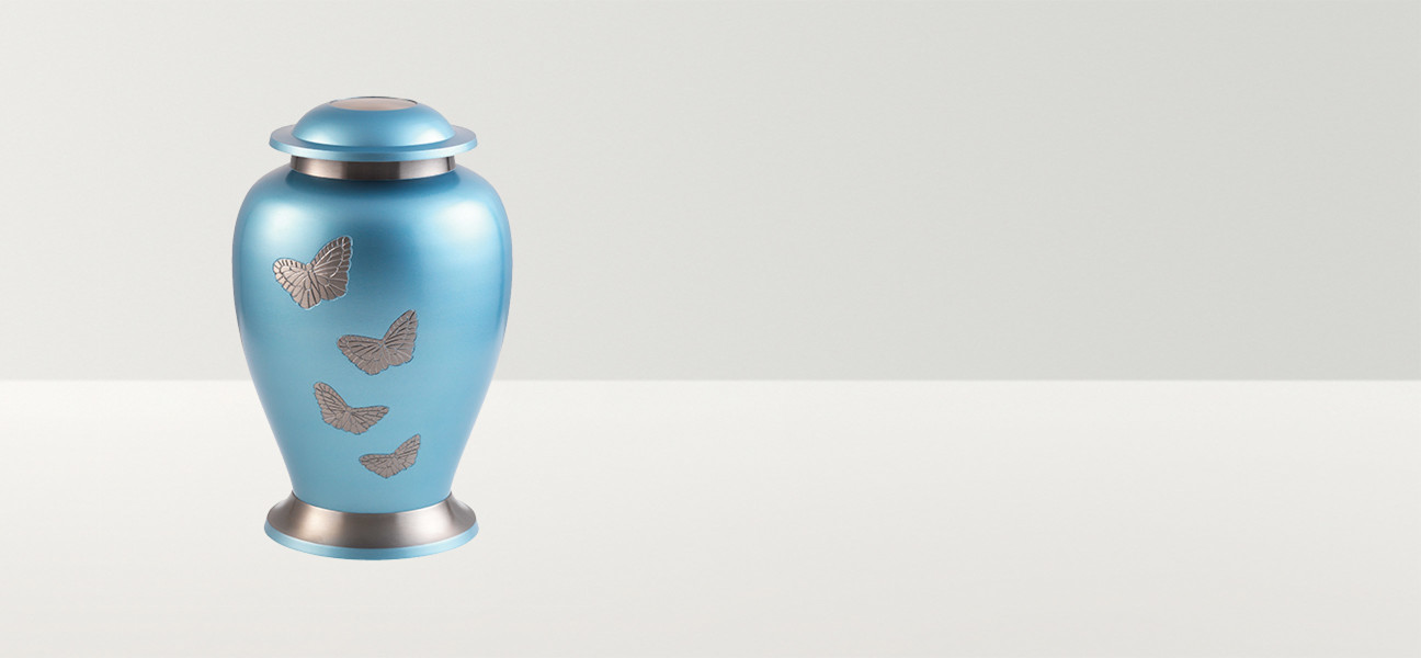 Pale blue urn with silver butterflies and decoration